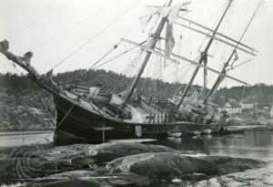 Svart-kvitt bilete, grunnstøytt seglbåt, liggande skeivt i vasskorpa, svaberg i forgrune, hus, svaberg og skog i bakgrunnen