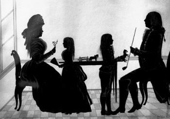Silhuett av familie, sittande ved bord, dame med hatt og blomsterkvast, jente med vifte, gut med leikehest, mann med lang pipe, leikehest med kjerre på bordet, rutete golv, vidauge til venstre