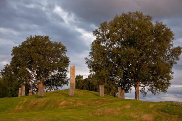 Grashaug, med bauta øvst, ni mindre bautaar med kjetting mellom, to lauvtre ved haugen, fleire i bakgrunnen, grå-blå skyar på himmelen